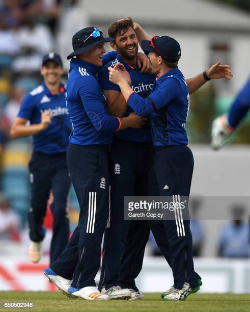 Liam Plunkett of England celebrates with teammates Eoin Morgan and Jason Roy after dismissing Jason Holder of the West Indies during the 3rd One Day...