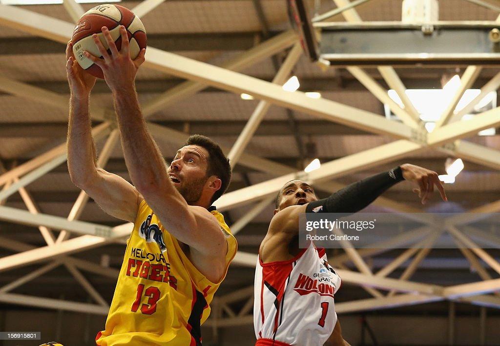 Liam Rush of the Tigers scores as Lance Hurdle of the Hawks attemptts to block during the round eight NBL match between the Melbourne Tigers and the Wollongong Hawks at State Netball Hockey Centre on November 25, 2012 in Melbourne, Australia.