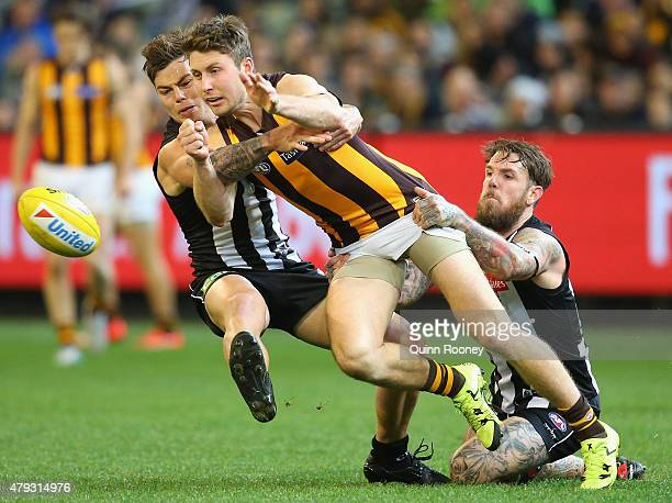 Liam Shiels of the Hawks handballs whilst being tackled by Jamie Elliott and Dane Swan of the Magpies during the round 14 AFL match between the...