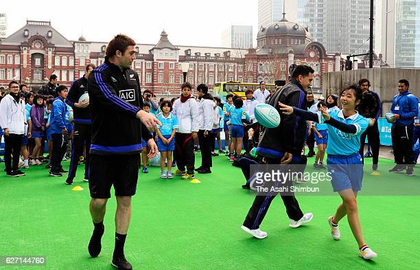 Liam Squire of All Blacks passes the ball during a session with children in front of Tokyo Station on December 1 2016 in Tokyo Japan
