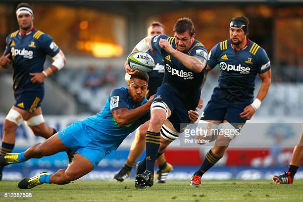 Liam Squire of the Highlanders is tackled by George Moala of the Blues during the round one Super Rugby match between the Blues and the Highlanders...