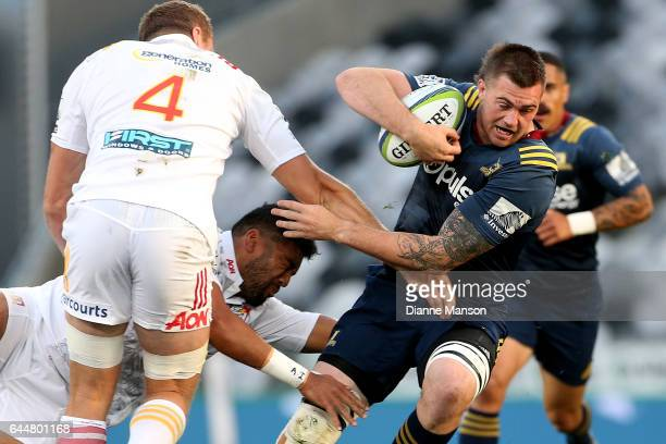 Liam Squire of the Highlanders tries to break through the tackle of Taleni Seu of the Chiefs during the round one Super Rugby match between the...
