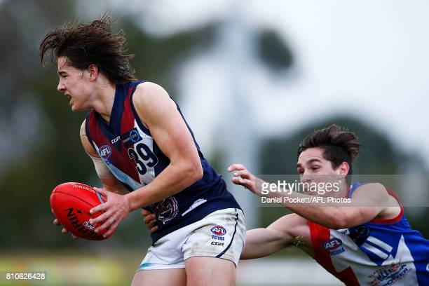 Liam Stocker of the Dragons is tackled by Austin Hodge of the Power during the round 12 TAC Cup match between Gippsland and Sandringham at Casey...