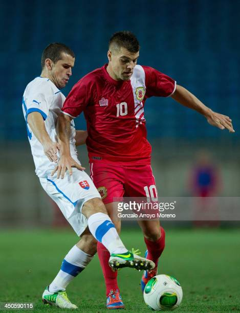 Liam Walker of Gibraltar competes for the ball with Viktor Pecovsky of Slovakia during the international friendly match between Gibraltar and...