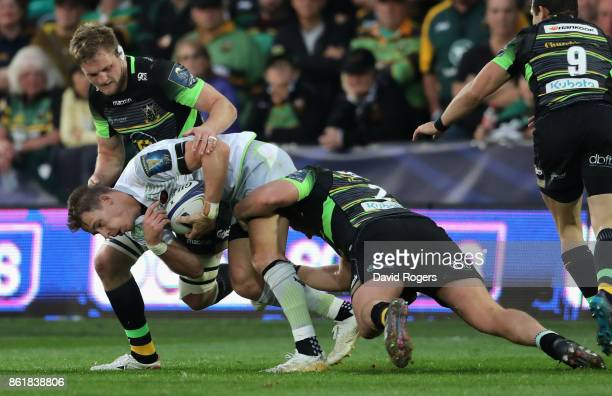 Liam Wiliams of Saracens is tackled by Jamie Gibson and Dylan Hartley during the European Rugby Champions Cup match between Northampton Saints and...