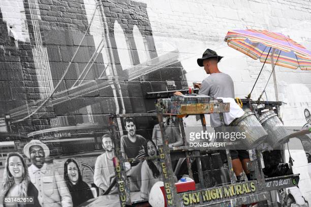 TOPSHOT Liam Williams an Expert painter for Colossal Media paints an ad on the side of Colossal Media's office building August 2 in New York Colossal...