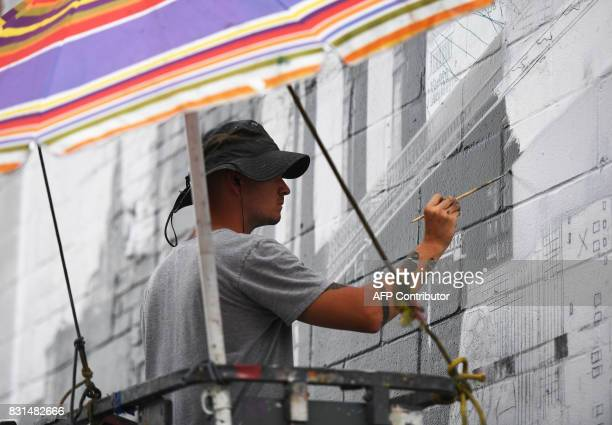 Liam Williams an Expert painter for Colossal Media paints an ad on the side of Colossal Media's office building August 2 in New York Colossal Media...