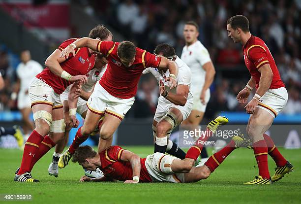 Liam Williams lies on the floor with the ball as Dan Biggar of Wales leaps over him during the 2015 Rugby World Cup Pool A match between England and...