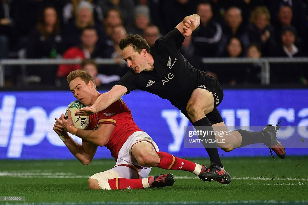 Liam Williams (L) of Wales is tackled by New Zealand's Ben Smith (R) during the third rugby union Test match between the New Zealand All Blacks and Wales at Forsyth Barr Stadium in Dunedin on June 25, 2016. / AFP / Marty Melville