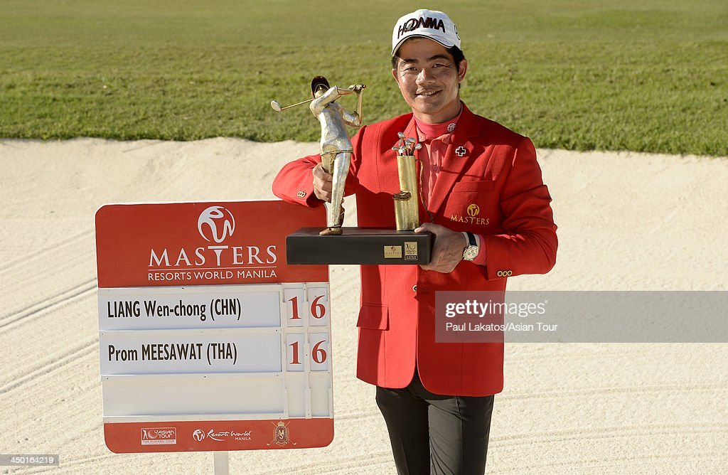 Liang Wen chong of China pictured with the winner's trophy after he defeated Prom Meesawat of Thailand in a playoff during round four of the Resorts World Manila Masters at Manila Southwoods Golf and Country Club on November 17, 2013 in Manila, Philippines.