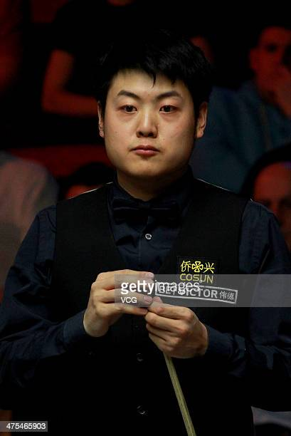 Liang Wenbo of China chalks his cue against Barry S Hawkins of England on day nine of The Welsh Open at the Newport Centre on February 27 2014 in...