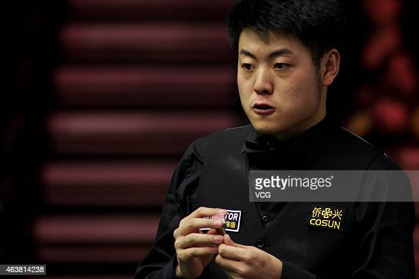 Liang Wenbo of China chalks his cue against John Higgins of Scotland during day three of 2015 BetVictor Welsh Open at Motorpoint Arena on February 18...