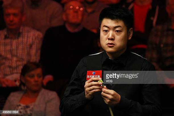 Liang Wenbo of China chalks his cue against Tom Ford of England in fourth round match on day nine of Betway UK Championship at Barbican Centre on...