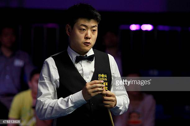 Liang Wenbo of China chalks his cue during his match against Mark Davis of England on day three of the 2014 Snooker Haikou World Open on March 12...