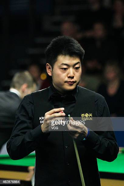 Liang Wenbo of China chalks his cue in his match against Ryan Day of Great Britain on day three of the 2015 German Masters at Tempodrom on February 6...