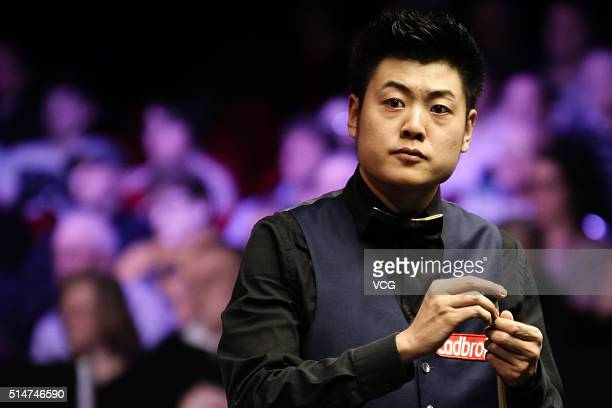 Liang Wenbo of China chalks his cue in the second round match against Michael Holt of England on day three of the Ladbrokes World Grand Prix at Venue...