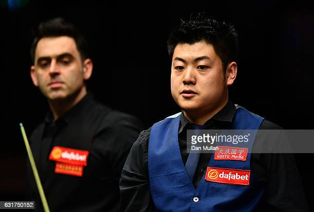 Liang Wenbo of China looks on alongside Ronnie O'Sullivan of England during their first round match on day one of the Dafabet Masters at Alexandra...