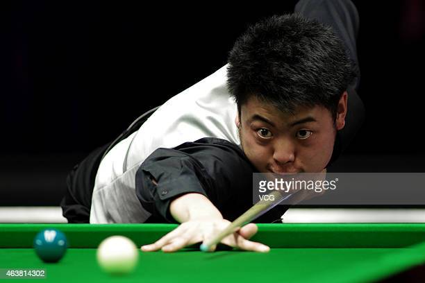 Liang Wenbo of China plays a shot against John Higgins of Scotland during day three of 2015 BetVictor Welsh Open at Motorpoint Arena on February 18...