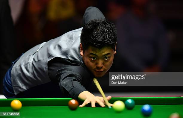 Liang Wenbo of China plays a shot during his first round match against Ronnie O'Sullivan of England on day one of the Dafabet Masters at Alexandra...