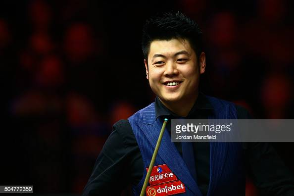 Liang Wenbo of China smiles in his first round match against John Higgins of Scotland during Day Four of the Dafabet Masters at Alexandra Palace on...