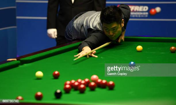 Liang Wenbo plays a shot against Stuart Carrington during their first round match of the World Snooker Championship at Crucible Theatre on April 18...