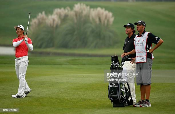 Liang Wenchong of China plays his approach to the 18th hole watched by Phil Mickelson of the USA during the final round of the WGCHSBC Champions at...