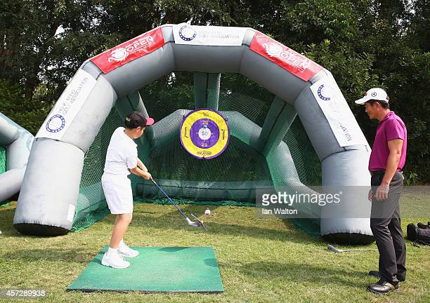 Liang WenChong of China takes part in a kids golf clinic during the first round of the 2014 Hong Kong open at The Hong Kong Golf Club on October 16...