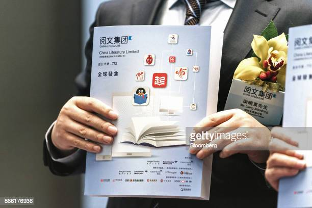 Liang Xiaodong cochief executive officer and executive director of China Literature Ltd holds an information booklet for a photograph during a news...