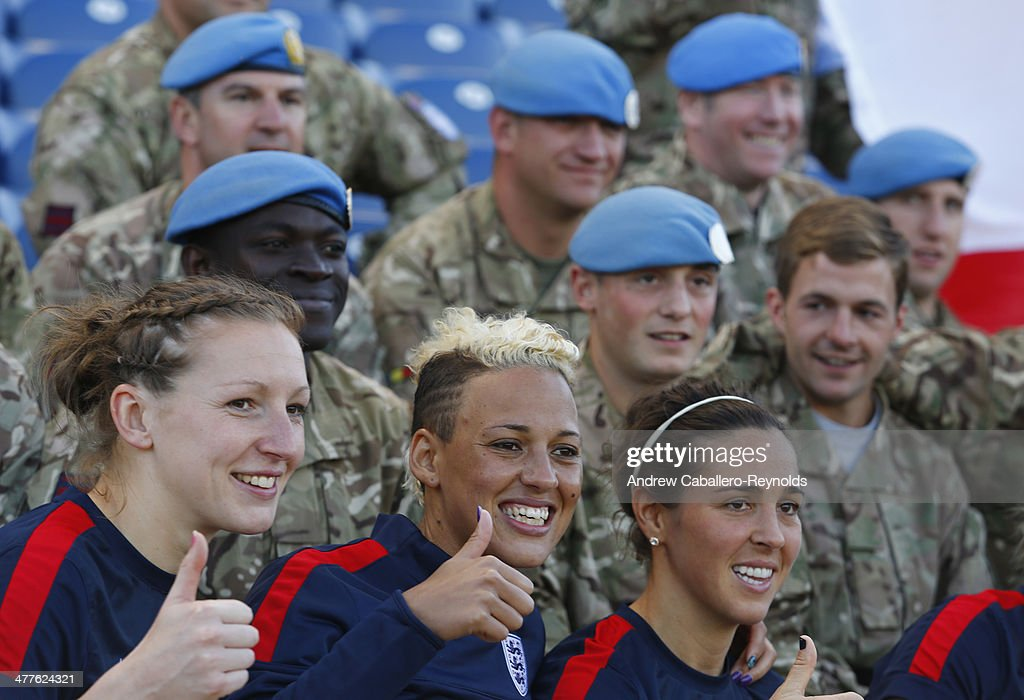 Lianne Sanderson (C) of England and teammates pose for a photo with UN Peacekeeprs from the UK after the Cyprus Cup match between England and Canada at GSP stadium on March 10, 2014 in Nicosia, Cyprus.