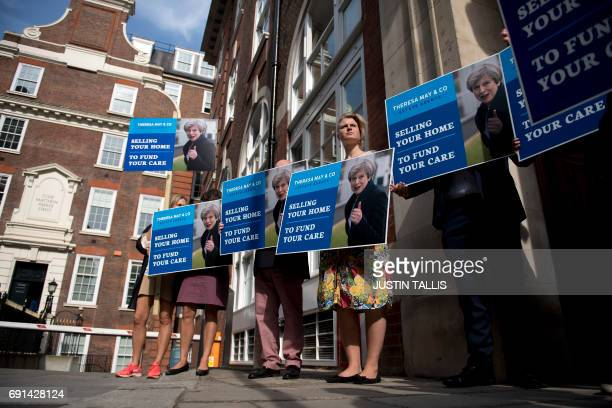 Liberal Democrat campaigners carry placards as they demonstrate against British Prime Minister Theresa May's social care policy or 'Dementia Tax' in...