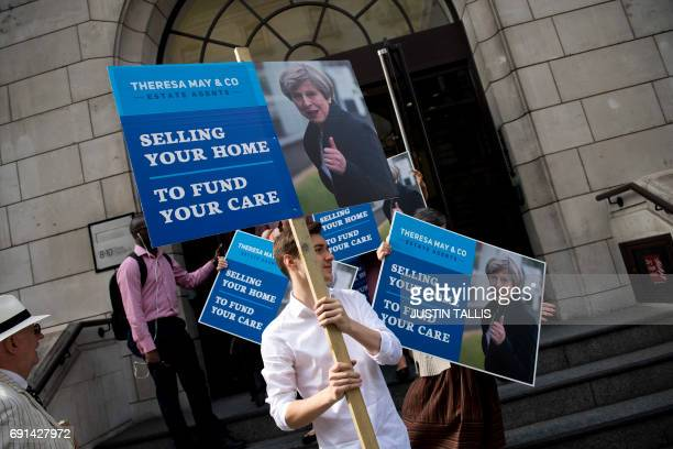 Liberal Democrat campaigners carry placards as they leave the party headquarters to demonstrate against British Prime Minister Theresa May's social...