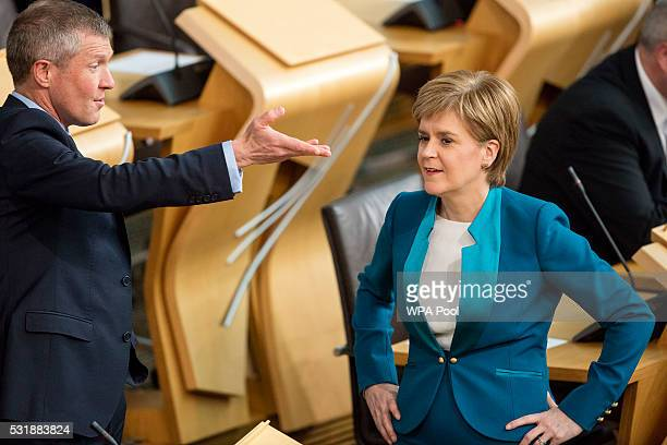 Liberal Democrat leader in Scotland Willie Rennie chats with First Minister of Scotland Nicola Sturgeon in the Scottish parliament before Ms Sturgeon...