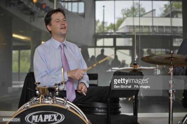 Liberal Democrat leader Nick Clegg plays the drums during a musical performance during his visit to the Remix music project for young people at...