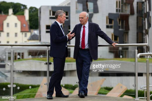 Liberal Democrat leader Vince Cable and Scottish party leader Willie Rennie pose for photographs with the Scottish Parliament in the background ahead...
