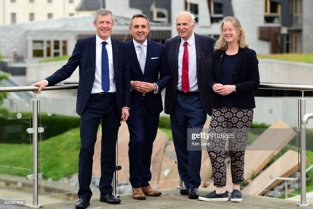 Liberal Democrat leader Vince Cable (2nd R) Scottish party leader Willie Rennie (L) Alex Cole-Hamilton MSP (2nd L) and Councillor Hal Osler (R) pose for photographs with the Scottish Parliament in the background ahead of a Scottish Liberal Democrat party event, on August 18, 2017 in Edinburgh, Scotland.