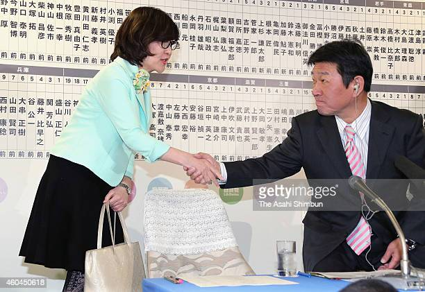 Liberal Democratic Party Policy Research Council chairwoman Tomomi Inada and election bureau chief Toshimitsu Motegi shake hands at the party...