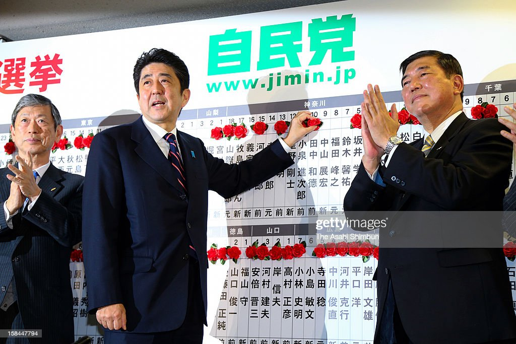Liberal Democratic Party (LDP) president <a gi-track='captionPersonalityLinkClicked' href=/galleries/search?phrase=Shinzo+Abe&family=editorial&specificpeople=559017 ng-click='$event.stopPropagation()'>Shinzo Abe</a> atteches a paper rose to the names of the LDP-backed candidates who secured the seat in the lower house while LDP secretary general <a gi-track='captionPersonalityLinkClicked' href=/galleries/search?phrase=Shigeru+Ishiba&family=editorial&specificpeople=2921096 ng-click='$event.stopPropagation()'>Shigeru Ishiba</a> claps his hands at their headquarters on December 16, 2012 in Tokyo, Japan. The LDP and coalition New Komeito gained 325 seats at the lower house and return to power while ruling DPJ made the historical defeat, dropped to 57 seat.
