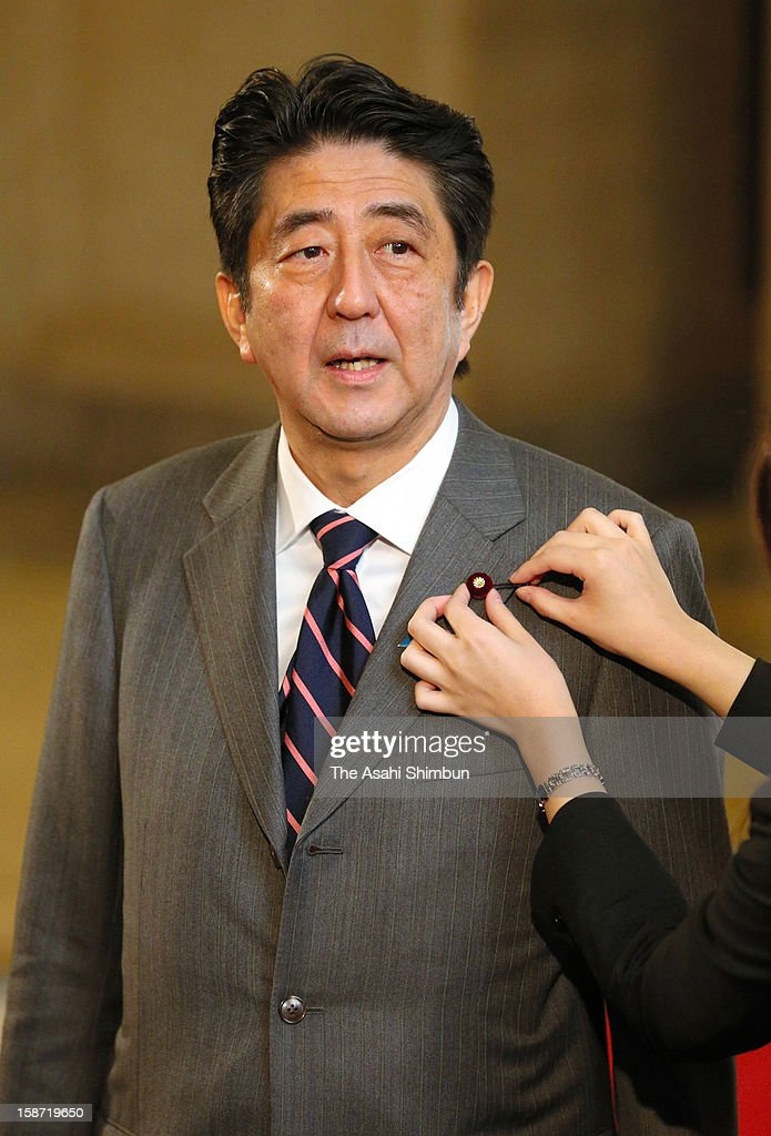 Liberal Democratic Party president <a gi-track='captionPersonalityLinkClicked' href=/galleries/search?phrase=Shinzo+Abe&family=editorial&specificpeople=559017 ng-click='$event.stopPropagation()'>Shinzo Abe</a> is attached the lawmaker's budge at the lower house at the diet building on December 26, 2012 in Tokyo, Japan. Abe becomes Japan's 96th prime minister, seventh in six years.
