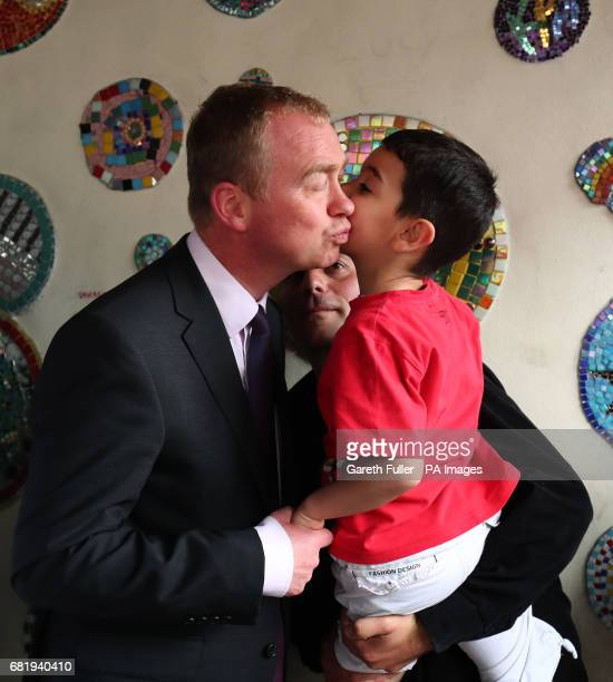 Liberal Democrats leader Tim Farron is kissed goodbye by a young refugee from Syria during a visit to charity Gloustershire Action for Refugess and...