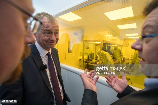 Liberal Democrats party leader Tim Farron speaks to principal consultant Hans Hoppe outside a laboratory where scientists are working microchannel...
