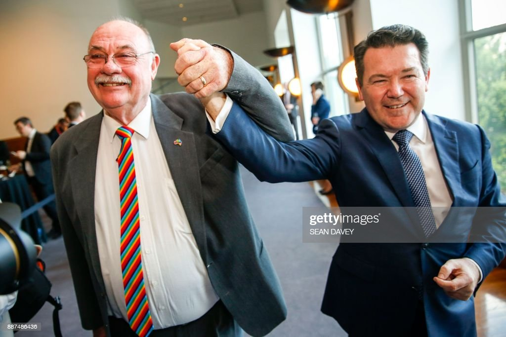Liberal Members of Parliament Warren Entsch (L) and Den Smith celebrate after parliament passed the same-sex marraige bill in the Federal Parliament in Canberra on December 7, 2017. Gay couples will be able to legally marry in Australia after a same-sex marriage bill sailed through parliament on December 7, ending decades of political wrangling. /