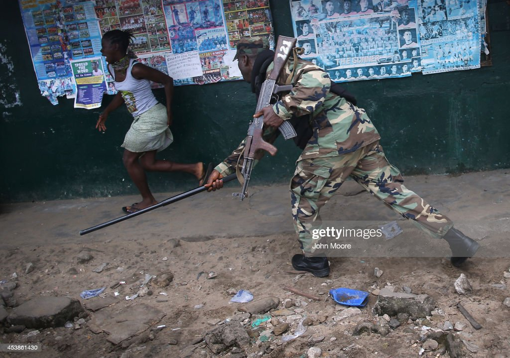 A Liberian Army soldier, part of the Ebola Task Force, beats a local resident while enforcing a quarantine on the West Point slum on August 20, 2014 in Monrovia, Liberia. The government ordered the quarantine of West Point, a congested seaside slum of 75,000, on Wednesday, in an effort to stop the spread of the virus in the capital city. Liberian soldiers were also sent in to the seaside favela to extract West Point Commissioner Miata Flowers and her family members after residents blamed the government for setting up a holding center for suspected Ebola patients to be set up in their community. A mob overran and closed the facility on August 16. The military also began enforcing a quarrantine on West Point, a congested slum of 75,000, fearing a spread of the epidemic. The Ebola virus has killed more than 1,200 people in four African nations, more in Liberia than any other country.