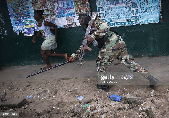 Liberian Army soldier part of the Ebola Task Force beats a local resident while enforcing a quarantine on the West Point slum on August 20 2014 in...