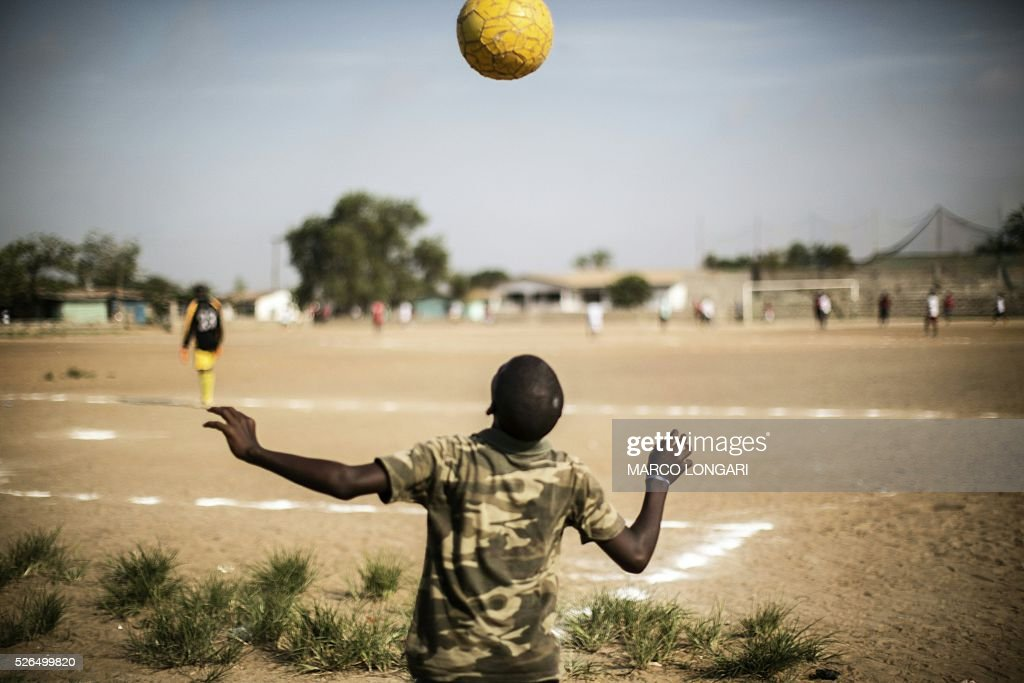 A Liberian boy plays with a ball as international Liberian soccer star, George Weah plays a match on a dusty pitch at the Alpha Old Timers Sports Association in Paynesville in Monrovia on April 30, 2016. Former international football star George Weah said on April 28, 2016, he would be a candidate in next year's presidential elections in Liberia, his second bid for the post. / AFP / MARCO