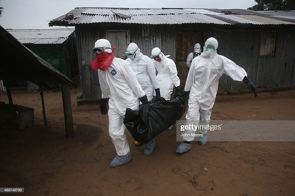 Liberian burial team wearing protective clothing retrieves the body of a 60yearold Ebola victim from his home on August 17 2014 near Monrovia Liberia...
