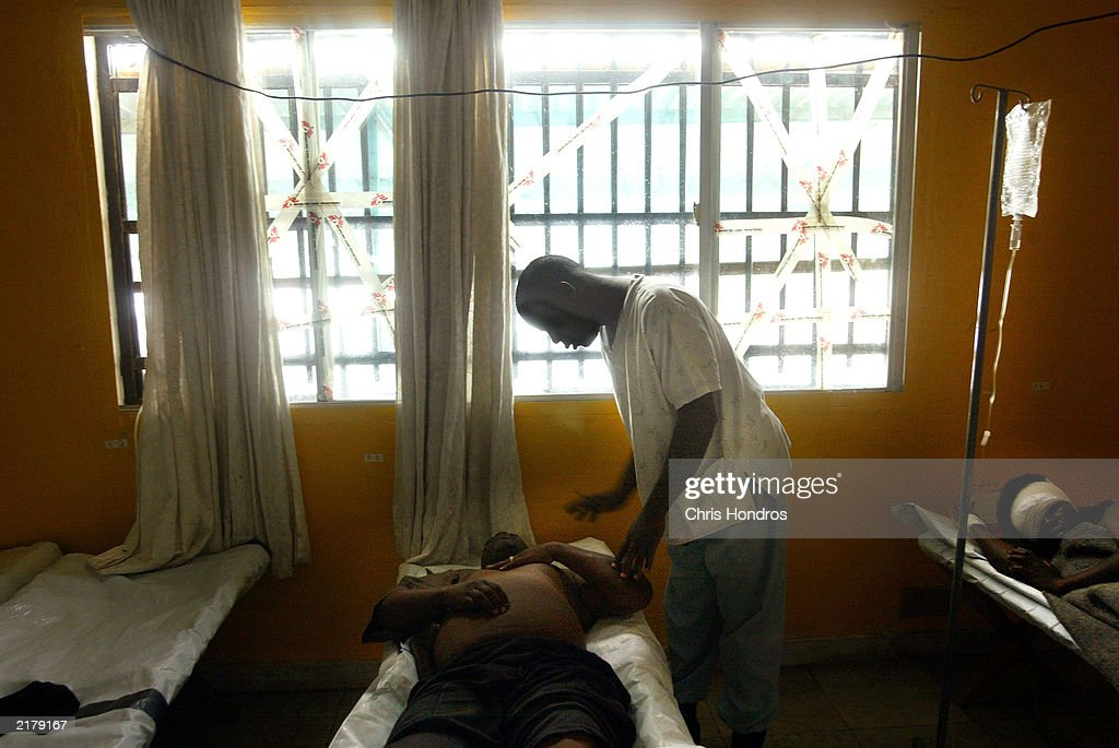 A Liberian doctor treats a wounded patient at a Doctors Without Borders hospital July 20, 2003 in Monrovia, Liberia. Government forces succeeded in forcing back rebel forces in fierce fighting on the edge of Monrovia's city center.