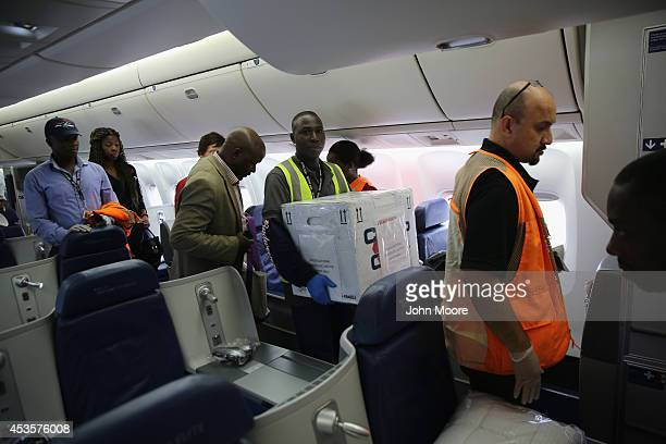 Liberian Foreign Affairs Minister Augustine Ngafuan and a porter bring boxes of an experimental Ebolafighting drug ZMapp on a Delta Airlines flight...