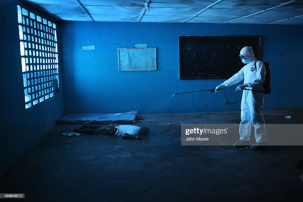 Liberian health worker disinfects a corpse after the man died in a classroom now used as Ebola isolation ward on August 15 2014 in Monrovia Liberia...