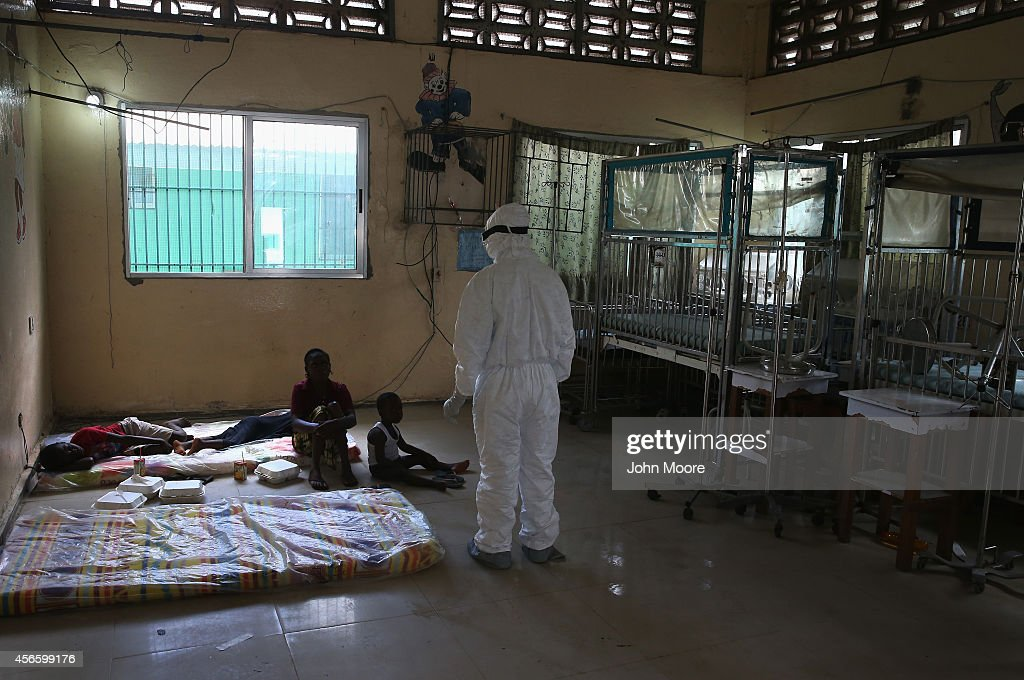 Liberian health worker dressed in an anticontamination suit speaks with a family in a holding center for suspected Ebola patients formerly the...