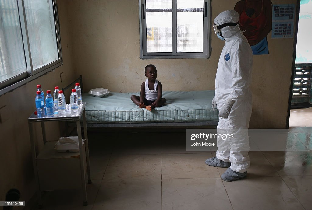 Liberian health worker dressed in an anticontamination suit speaks with a boy at a center for suspected Ebola patients formerly the maternity ward at...